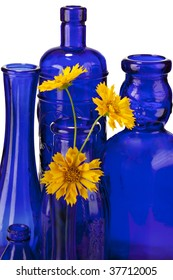 Beautiful cobalt blue bottles and vases with bright yellow flowers isolated on white