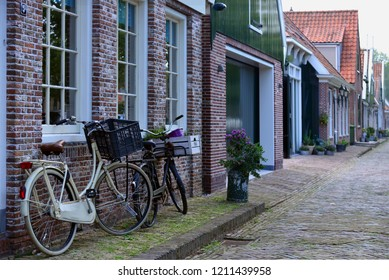 Beautiful cobbled street in Edam, with two bicicles supported on a red brick wall. Typical urban scene of Holland, with a row of colorful townhouses, in a cozy little village in Europe.