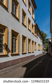 Beautiful cobblestone street with open stylish windows with yellow frame in the famous travel destination Heidelberg, Germany, Europe. Shot on sunny in summer