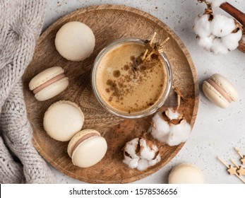 Beautiful coffee french macarons on wooden round plate with cup of morning coffee, cotton buds, wooden stars, cinnamon powder and warm pullover. Christmas and winter background, top view, flat layout