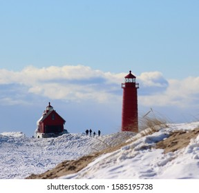 Beautiful cold sunny February day on Lake Michigan in Grand Haven looking out at the ice,sand and snow covered pier of silhouettes of tourists trekking along the red lighthouse and boat house.