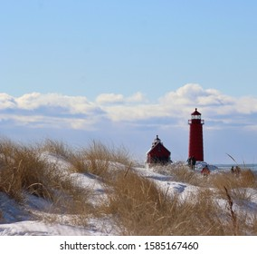 Beautiful cold sunny winters day standing on a sand dune of of dried sea grass at Grand Haven Michigan State park with a depth of field of the red Lighthouse, boathouse and visitors on the icy pier.