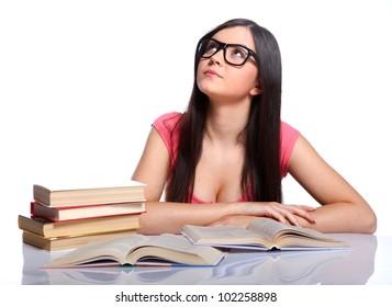 Beautiful college girl sitting in glasses near the books