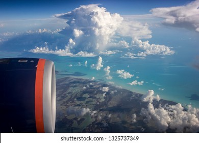 beautiful coloful sky scape shot of an airplane engine on a dark blue sky and amazing cotton candy white clouds with a piece of green land and turquoise ocean water beneath.