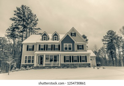 Beautiful colonial style American house covered in snow with split tone filter