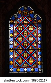 Beautiful colored ancient stained glass with a pattern of diamonds and castles
