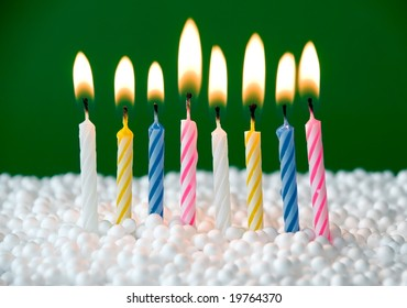 beautiful colored candles over a green background