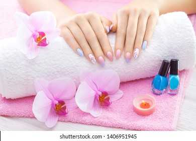 beautiful colored manicure with decor, orchid, towel and candle on the white wooden table. spa
