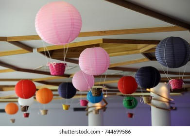 Beautiful colored paper lanterns hanging on the ceiling as air balloons