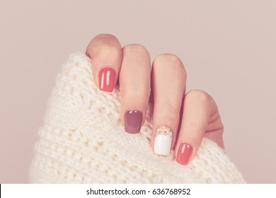 Beautiful colored pastel colors nail polish on hand, closeup. Nail art manicure concept
