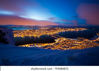 Beautiful and colorful aerial view on the city Tromso, Troms Norway, during dusk. A winter snowstorm is incoming in the valley of Tromso, eliminating the clear sky sunset.