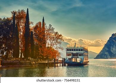 Beautiful and colorful autumn in riva del garda,Garda lake,The anchored boat in Riva del Garda , Lago di garda, italy