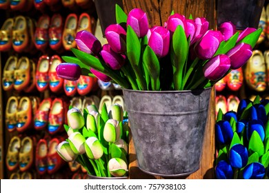 Beautiful colorful bouquets of wooden tulips in the bucket and wooden shoes in row on the wall. Dutch souvenir shop decoration in Zaanse Schans, Netherlands, Europe