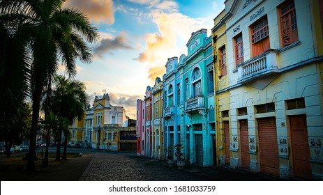 Beautiful colorful buildings during a colorful sunset down a small cobblestone road located downtown in the tropical city of Joao Pessoa, Brazil.