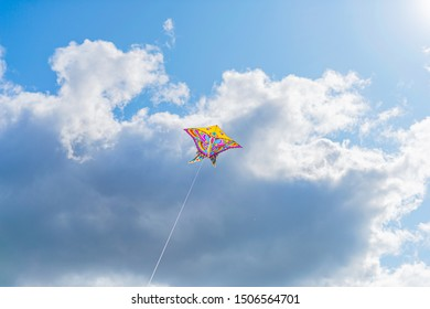 Beautiful colorful butterfly kite against the sky and clouds, freedom vacation travel concept