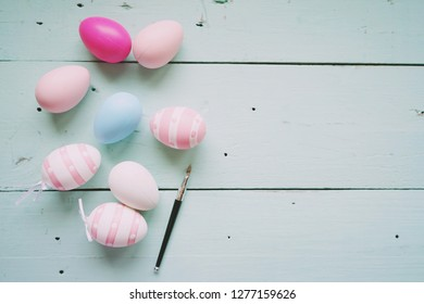A beautiful and colorful close-up flat of isolated easter eggs in plain colors and striped by a small brush over a pastel blue wooden table with space