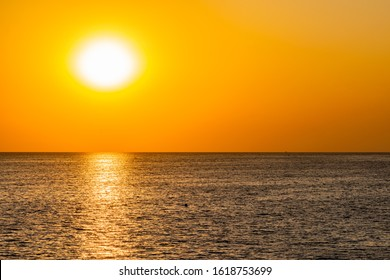 Beautiful, colorful and contrasting sunset over the sea, ocean. The hot sun illuminates the spacious landscape, throwing the glare of rays on the water surface. The bright sun splash at adventure trav