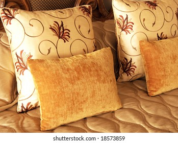 Beautiful colorful cushions on bed in guest lodge