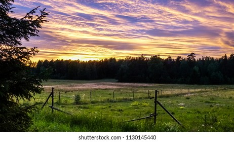 Beautiful, colorful and dramatic sky at sunset. Silhouette of forest and pasture / horse paddock in the foreground.
