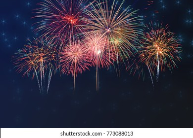 Beautiful colorful fireworks display for celebration on dark background with blur stars,  New year holiday concept