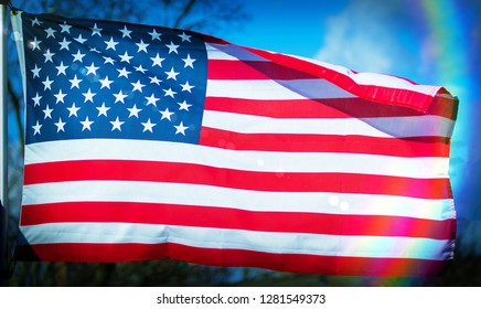 Beautiful colorful fully unfurled American flag with lens flare and rainbow spectrum