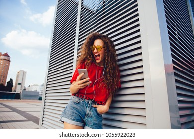 Beautiful colorful girl looking at smartphone screen, watching funny video, cheerfully laughing, while walking on the city street.