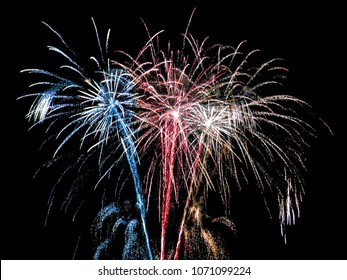 Beautiful colorful holiday fireworks in the evening. Patriotic red, white and blue sparkle. 4th of July. Historical background for celebrations and parties. Independence Day