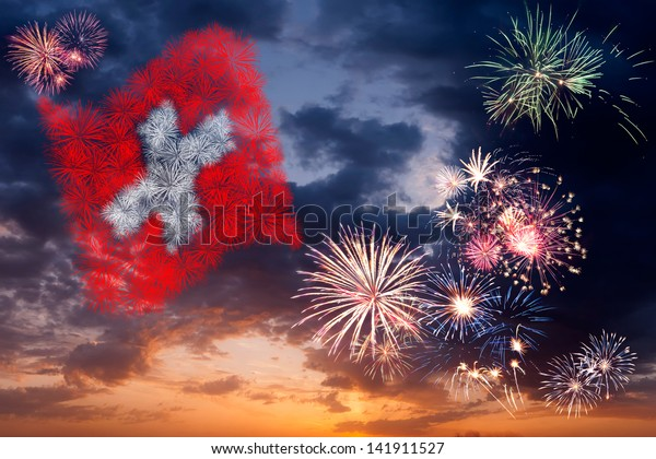 Beautiful colorful holiday fireworks with national flag of Switzerland, evening sky with majestic clouds