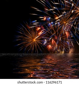 Beautiful colorful holiday fireworks with reflection on the black sky background, close-up, long exposure