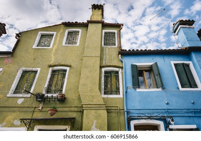 Beautiful colorful house facade on Burano island, north Italy. Olive colored old damaged house wall and blue wall with windows on it, view from below