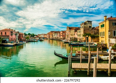Beautiful colorful image of a canal in Venice with moorings and a gondola in the forefront and old houses under blue cloudy sky in the background.