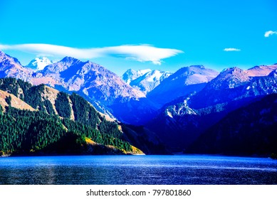 Beautiful colorful landscape of lake mountain in the alps with green trees, glacier and blue sky background in the morning.