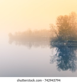 A beautiful, colorful misty morning in Norway at the lake. Tree reflections in the water. Misty autumn landscape. Calm nordic scenery.