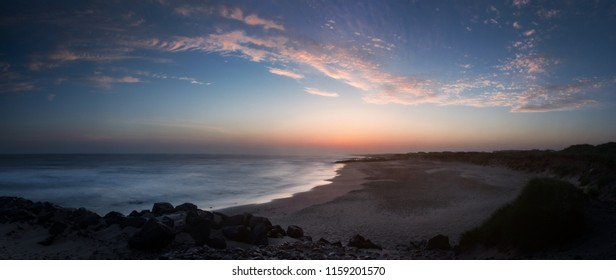 Beautiful and colorful morning twilight panorama with moody purple clouds at the danish North sea beach. Danish coastline , Lønstrup in North Jutland in Denmark, Skagerrak, North Sea