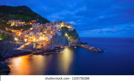 Beautiful colorful panoramic photo of village Manarola by night in Cinque Terre, Italy.