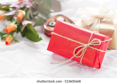 Beautiful colorful pretty gift or present in a natural paper with chocolate pralines, coffee and fresh roses on a bed. Holiday, valentine's day or surprise concept