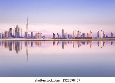 Beautiful colorful purple and pink sunrise lighting up the skyline and the reflection of Dubai Downtown. Dubai, United Arab Emirates.
