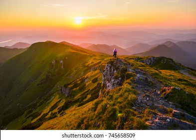 Beautiful colorful scenery in mountains - alone woman looking at sunset sky
