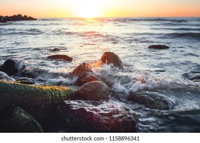 Beautiful and colorful seascape of waves rolling and splash on wet rocks in the danish coastline. Danish Beach, Lønstrup in North Jutland in Denmark, Skagerrak, North Sea