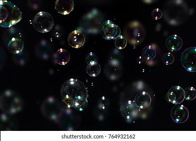 Beautiful colorful soap bubbles floating in the dark, black background