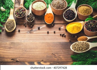 Beautiful colorful spices in spoons and bowls on an old wooden brown table and fresh green dill. Free space for your text