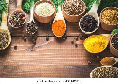 Beautiful colorful spices in wooden spoons and bowls on an old brown table. Free space for your text