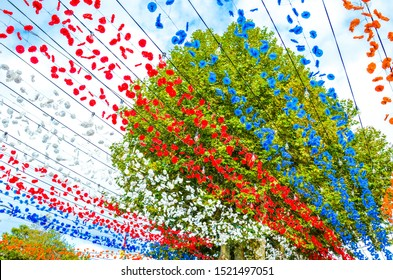 Beautiful colorful street decoration in Loreto, Madeira, Portugal. Celebration of the religious festival. Red, white, blue and orange paper flowers hanging in the air. Green tree in the background.