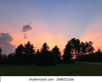 Beautiful, colorful sun rays illuminating a Saskatchewan sky at sunset