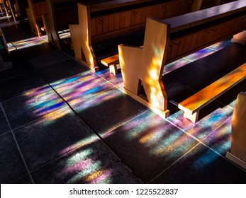 Beautiful colorful sunlight window reflections on the pews and the floor of the Church