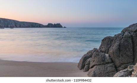 Beautiful colorful sunrise landscape image of Porthcurno beach on South Cornwall coast in England
