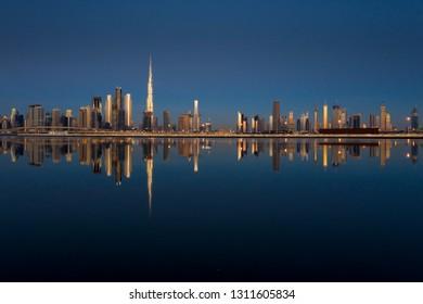 Beautiful colorful sunrise lighting up the skyline and the reflection of Dubai Downtown. Dubai, United Arab Emirates.