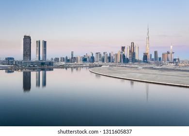 Beautiful colorful sunrise lighting up the skyline and the reflection of Dubai Downtown and D3 Dubai Design District. Dubai, United Arab Emirates.