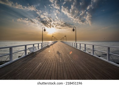 Beautiful colorful Sunrise on the pier at the seaside, Gdynia Orlowo, Poland. Long exposure photography. HDR photo. People on the pier.