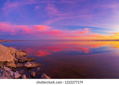 Beautiful colorful sunset in a calm Salton Sea lake in California.